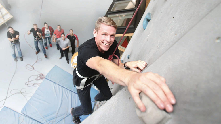 A young man climbs up a climbing wall