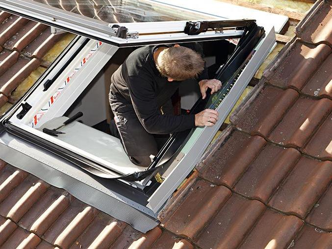 A craftsman installing a roof window