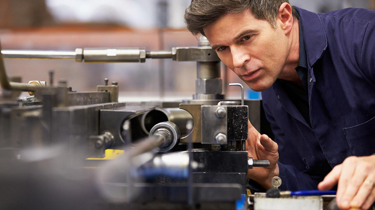 A man takes a close look at a part of a machine.